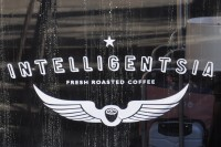 "The word ""Intelligentsia"" written over a pair of wings, bracketing the words ""Fresh Roasted Coffee"", all in white."