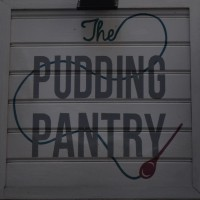 Detail from the sign hanging outside Nottingham's The Pudding Pantry