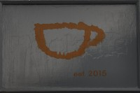 "A stylised outline of a cup in orange paint, with the words ""est. 2015"" underneath."