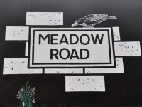 "The words ""Meadow Road"" written as is on a street sign, in black on a white background, while perched on top is a black and white line drawing of a bird with a coffee bean in its beak."