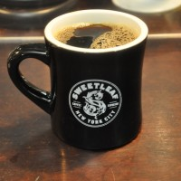 A mug of black filter coffee in a classic black American diner mug, adorned with Sweatleaf's logo.