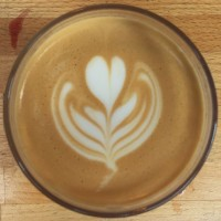 A flat white, seen from above, with a simple tulip pattern latte art.