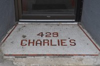 "The tiling in front of the door at Charlie's Sandwich Shoppe: small, white, square tiles with the number ""429"" above ""CHARLIE'S"" spelt out in red and black tiles."