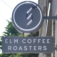 The Elm Coffee Roasters sign, hanging outside on a sunny Seattle day.