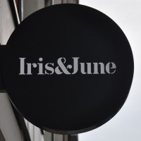"A black circle with the words ""Iris&June"" written in white inside it"