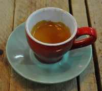 A classic espresso in a red cup on a green saucer.
