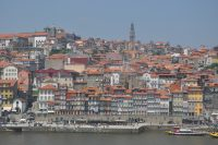 A view of Porto from across the Douro, with the Ribeira in the foreground at the river's edge and the Torre dos Clérigos at the top of the hill.