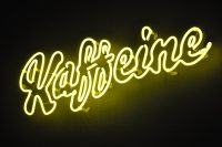 "The word ""Kaffeine"" written in a cursive script at an angle of 30 degrees to the horizontal"