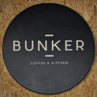 "The word BUNKER written in white, in the centre of a large black circle, with the smaller words ""COFFEE & KITCHEN"" written below/"