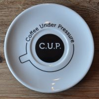 "A saucer, seen above, with the outline of a cup drawn on the base of the saucer. The words ""Coffee Under Pressure"" are written around the circumference of the outline. In the centre is a black circle with ""C.U.P."" written in white in the very centre."