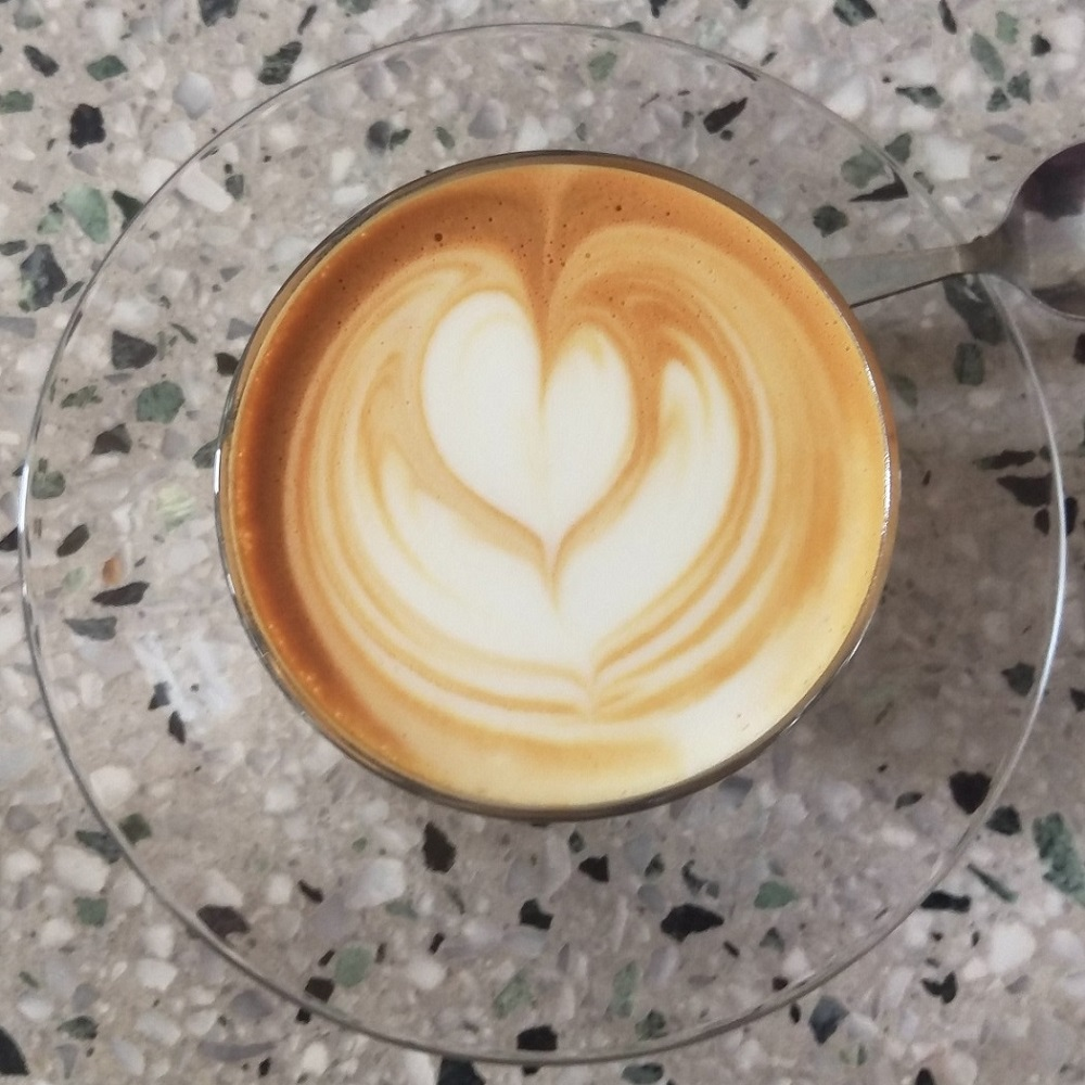 A piccolo with a tulip latte art pattern in a glass on a glass saucer, seen from directly above.