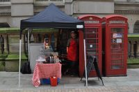 Jake's Coffee Box, occupying the left-hand of the two red telephone boxes, with a table out front, acting as a counter. Jake himself stands in the door, waiting his next customer.