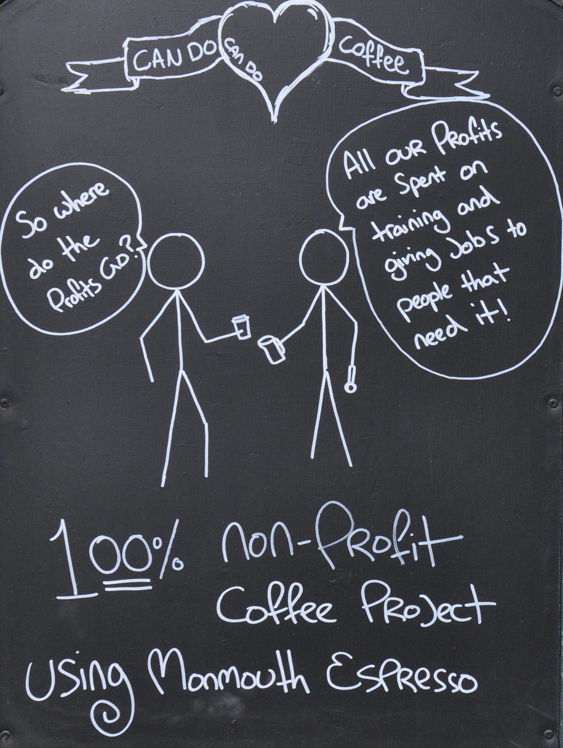 """An A-board showing two stick figures talking. The first asks """"So where do the profits go?"""" and the second answers """"All our profits are spent on training and giving jobs to people that need it!"""". Underneath it says """"100% non-profit coffee project using Monmouth espresso""""."""