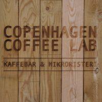 """Copenhagen Coffee Lab"" written above ""Kaffebar & Mikroristeri"" on an A-board made of five, vertical wooden planks."