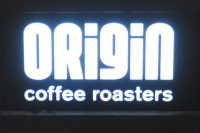 "The words ""ORigiN coffee roasters"" in illuminated white on a black background"