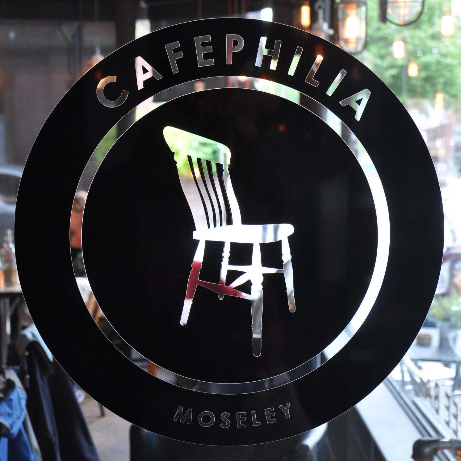 "A black circle, with a clear dining room chair in the centre. ""Cafephilia"" is written at the top of the circle and ""Moseley"" is written at the bottom."