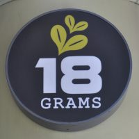 "The words ""18 GRAMS"" in white in a black circle. Some stylised coffee beans are drawn above the 18."