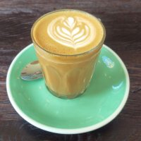A piccolo in a glass and on a green saucer, made with the guest espresso at 200 Degrees, Carrington Street.