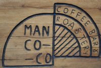 Detail from the wooden board outside the ManCoCo coffee bar and roastery in Manchester.