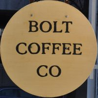 "The words ""Bolt Coffee Co"" written in a circular wooden sign."