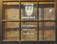 The sign, painted on an old window, on the back wall at Ultimo Coffee's Newbold coffee shop.