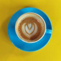 My flat white at Stanley & Ramona, in a blue cup on a yellow table, with the latte art surviving to the bottom of the cup.