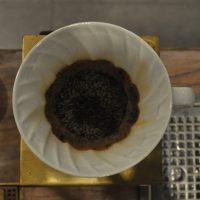 The flat bed of coffee grounds after brewing in a V60 at Vietnam Coffee Republic.