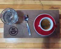 An espresso, plus a glass of sparkling water, beautifully presented at 5th Element Coffee in Madison.