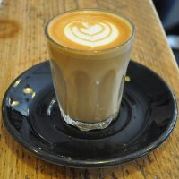 A lovely flat white from Brew Coffee Co, made with a Honduran single-origin, roasted by Clifton Coffee Co, and served in a glass.