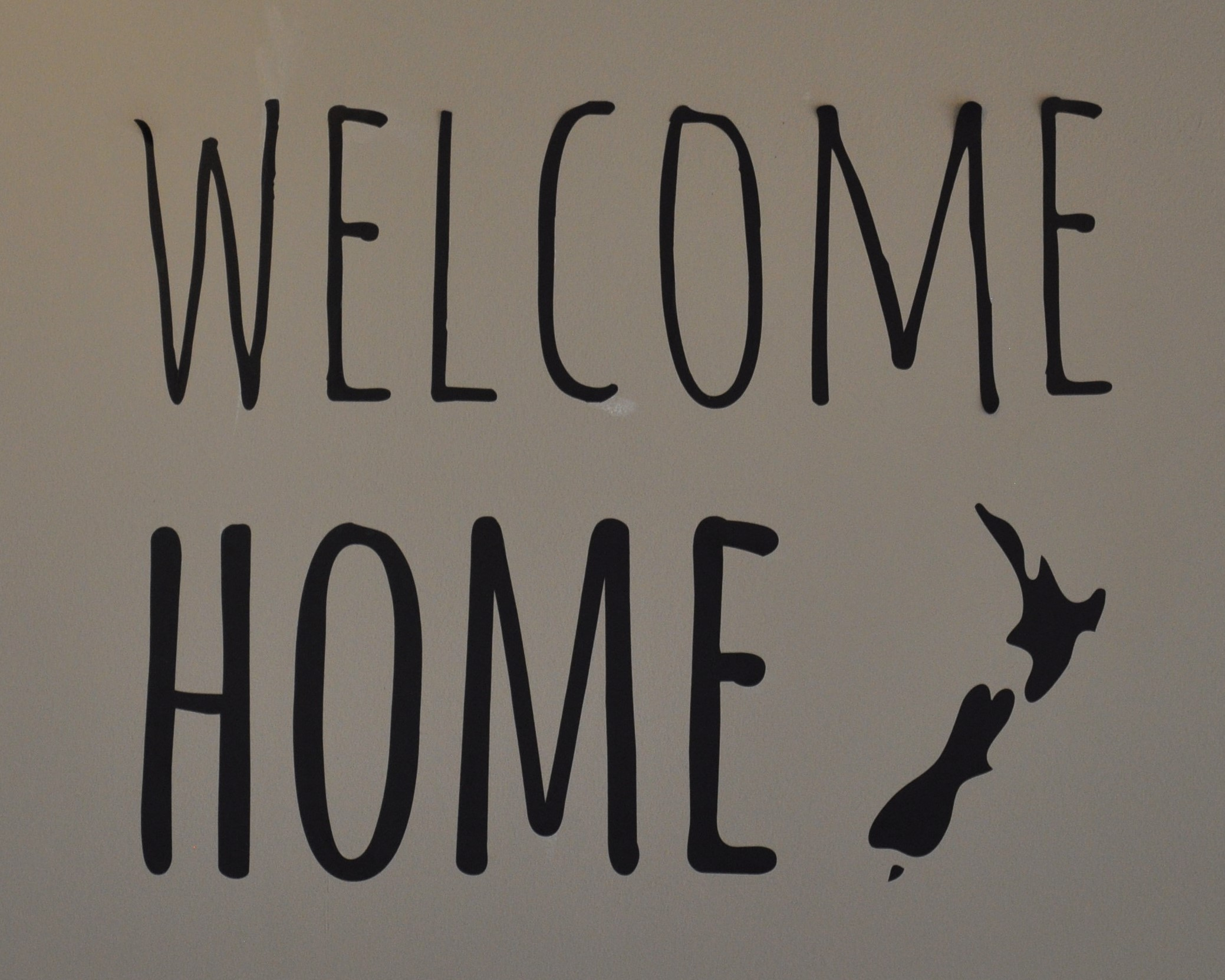 """Welcome Home"" says the sign on the wall of Eden Cafe in Witney, next to a stylised map of New Zealand."