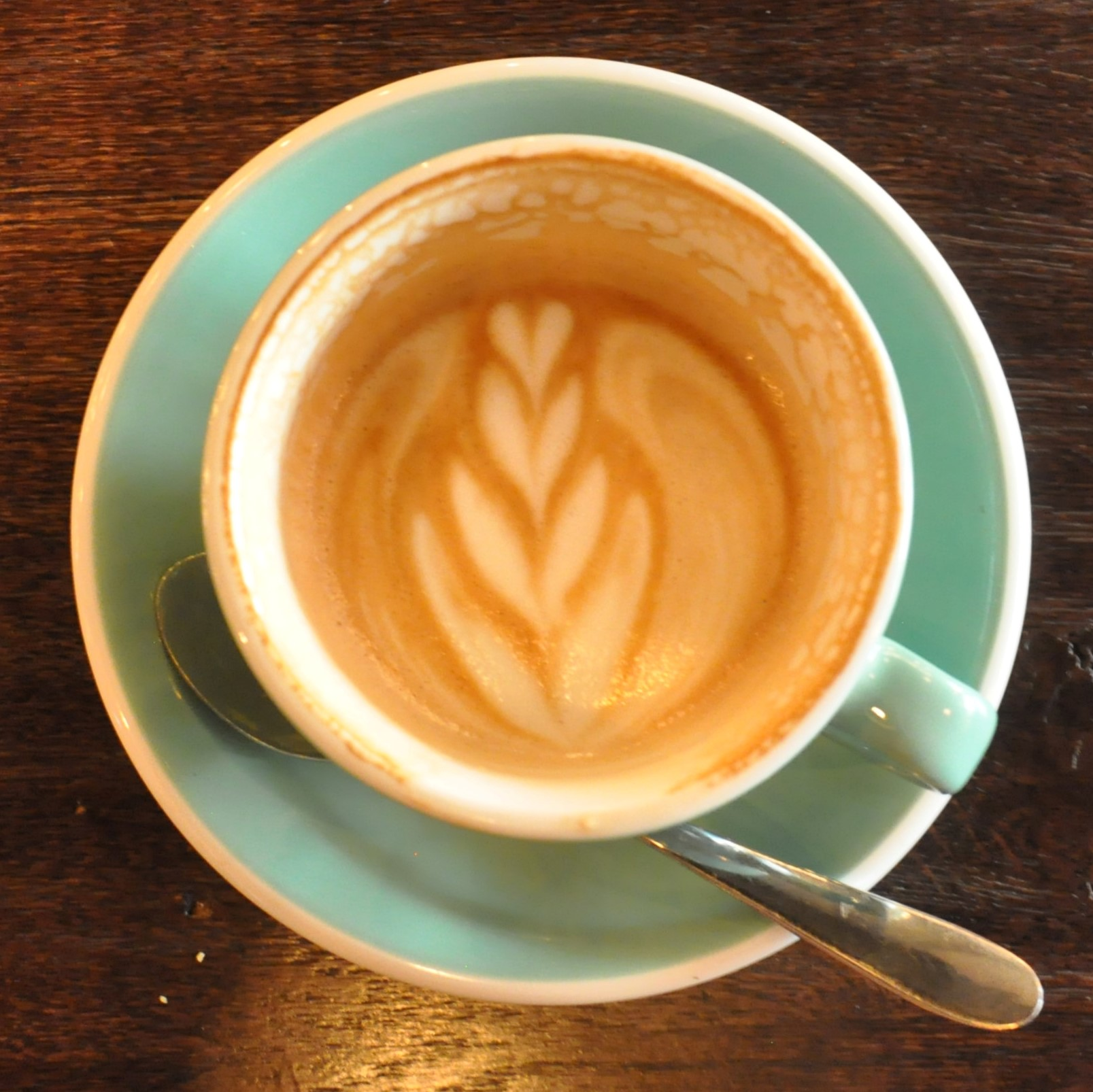 A decaf flat white at the Cardiff branch of 200 Degrees. The latte art pattern in the milk is still visible when half the coffee has been drunk.