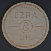 The Ezra & Gill logo etched in wood from the wall of Ezra To Go on Tib Street.
