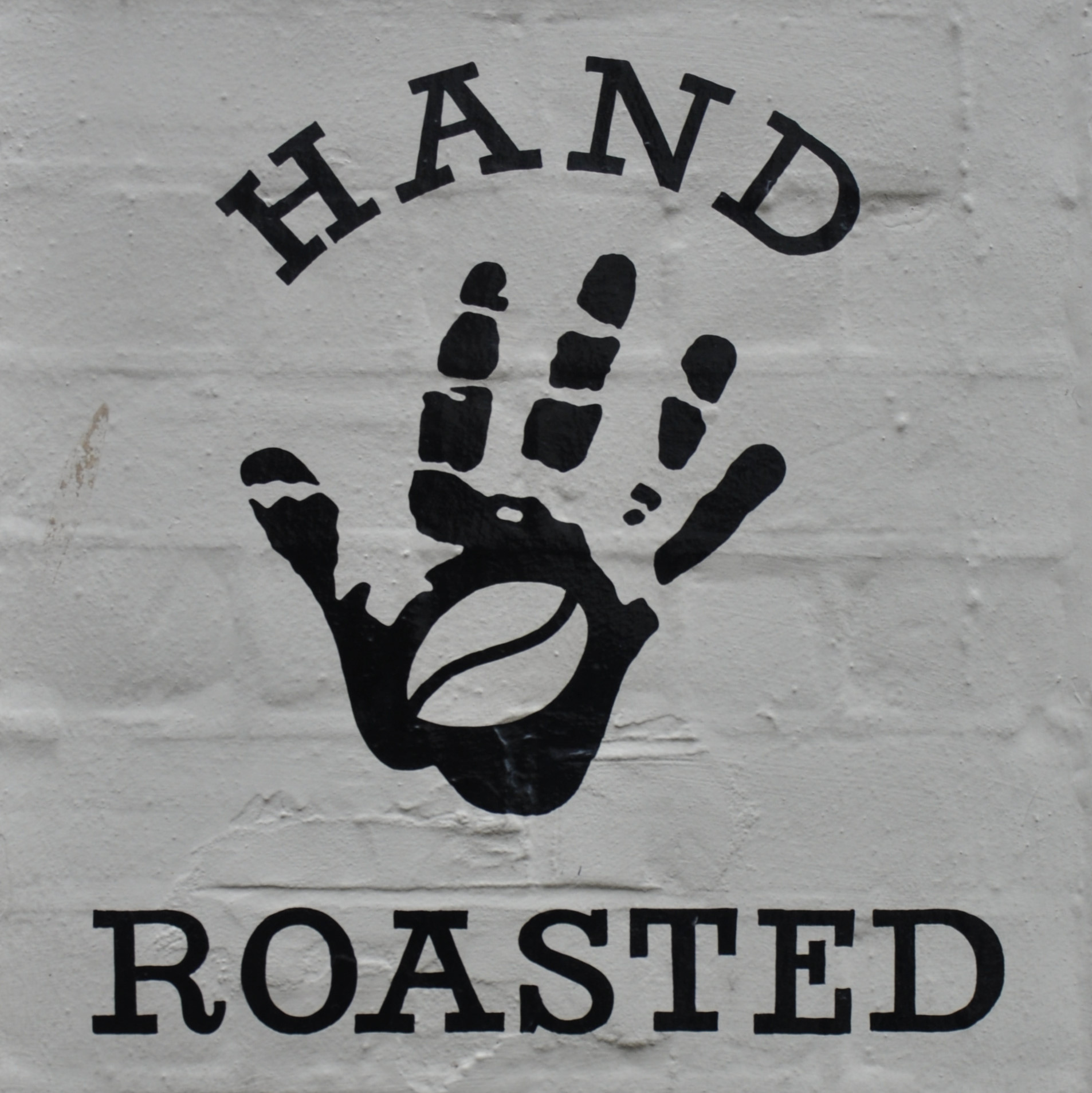 "A sign on the wall at the front of the Micro Roastery in Canterbury, a hand-print with the words ""Hand Roasted""."