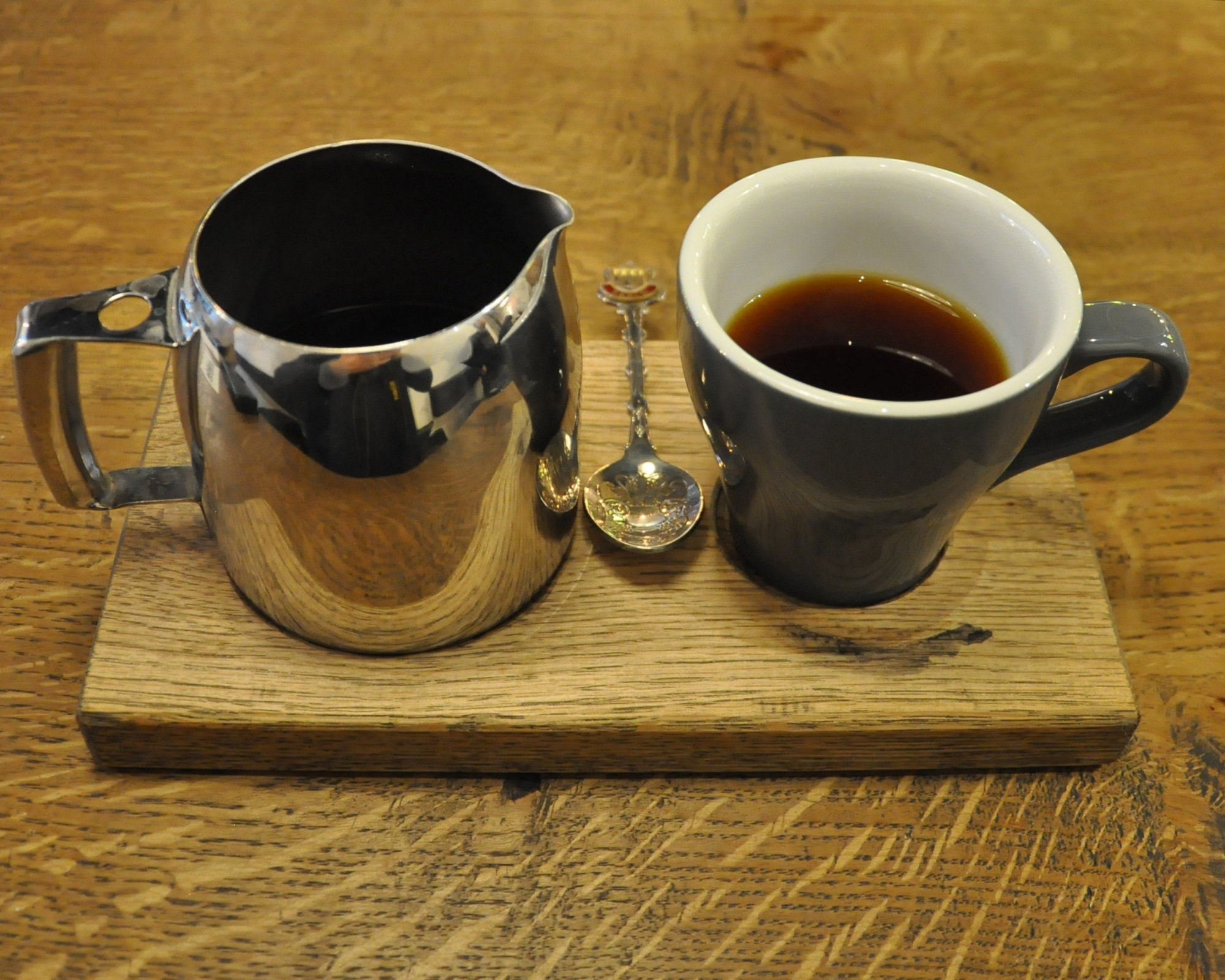 A beautifully-presented filter coffee at TAP, Russell Square, served on a wooden tray with the coffee in a metal jug and a tulip cup on the side.