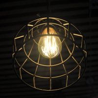 A bare light bulb in a wire cage, seen from below at Panther Coffee, Coconut Grove.