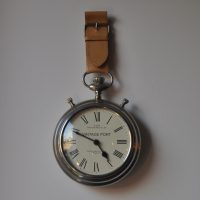 An over-sized pocket-watch, part of the Alice in Wonderland theme, which hangs on the wall by the door at The Pocket in Belfast.