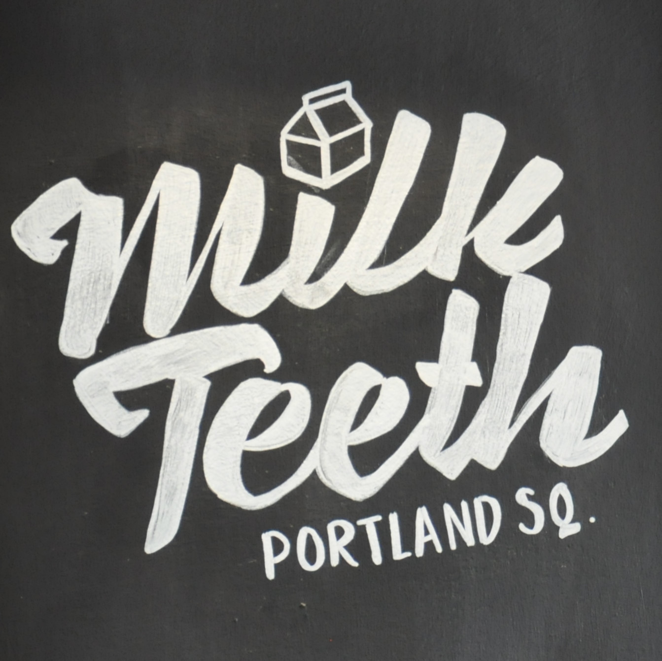 The Milk Teeth logo from the chalkboard just inside the door at Portland Square.
