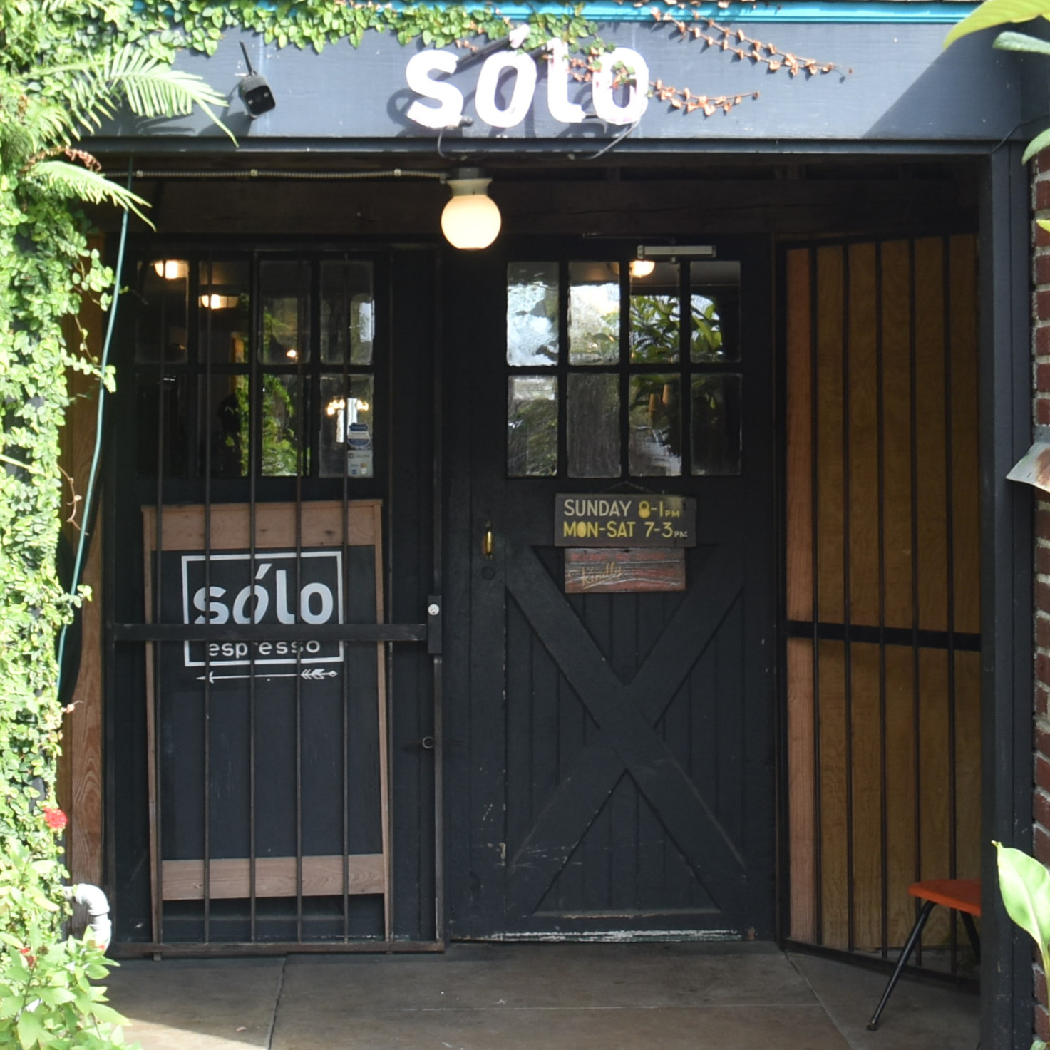 The recessed wooden double doors of Sólo Espresso in New Orleans.