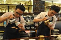 Synchronicity: two baristas pouring milk in cappuccinos at Shin Coffee, Ho Chi Minh City, VIetnam.