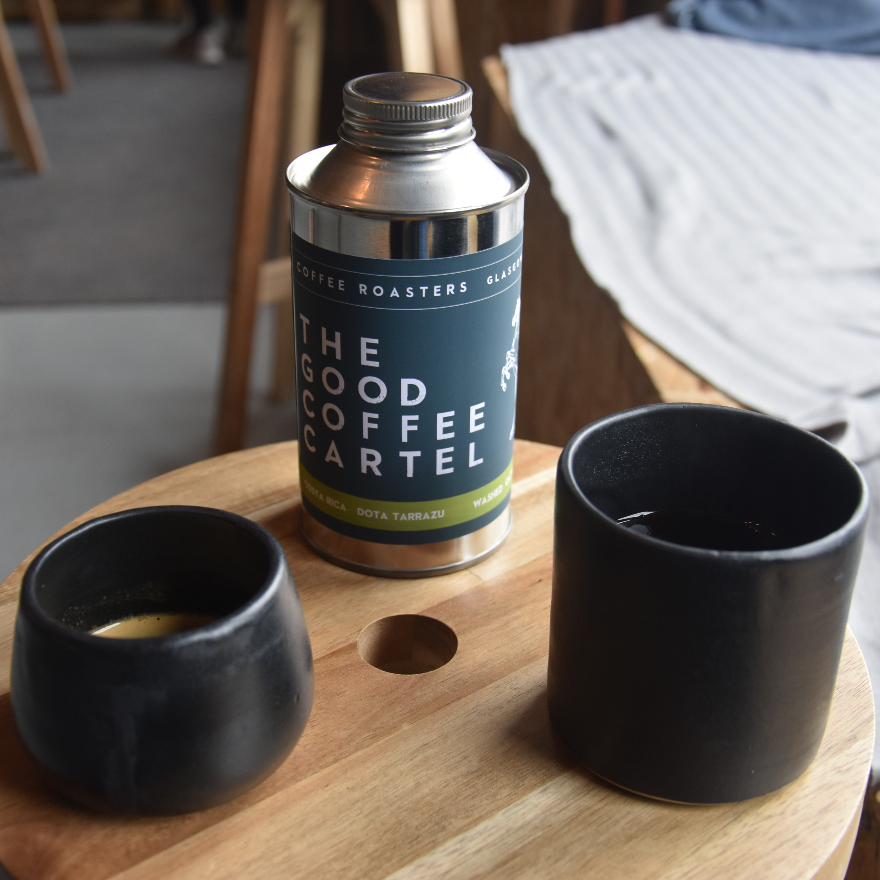 My espresso and batch-brew, both served in ceramic cups, handmade on-site at The Good Coffee Cartel, with a tin of the Costa Rican single-origin beans behind .