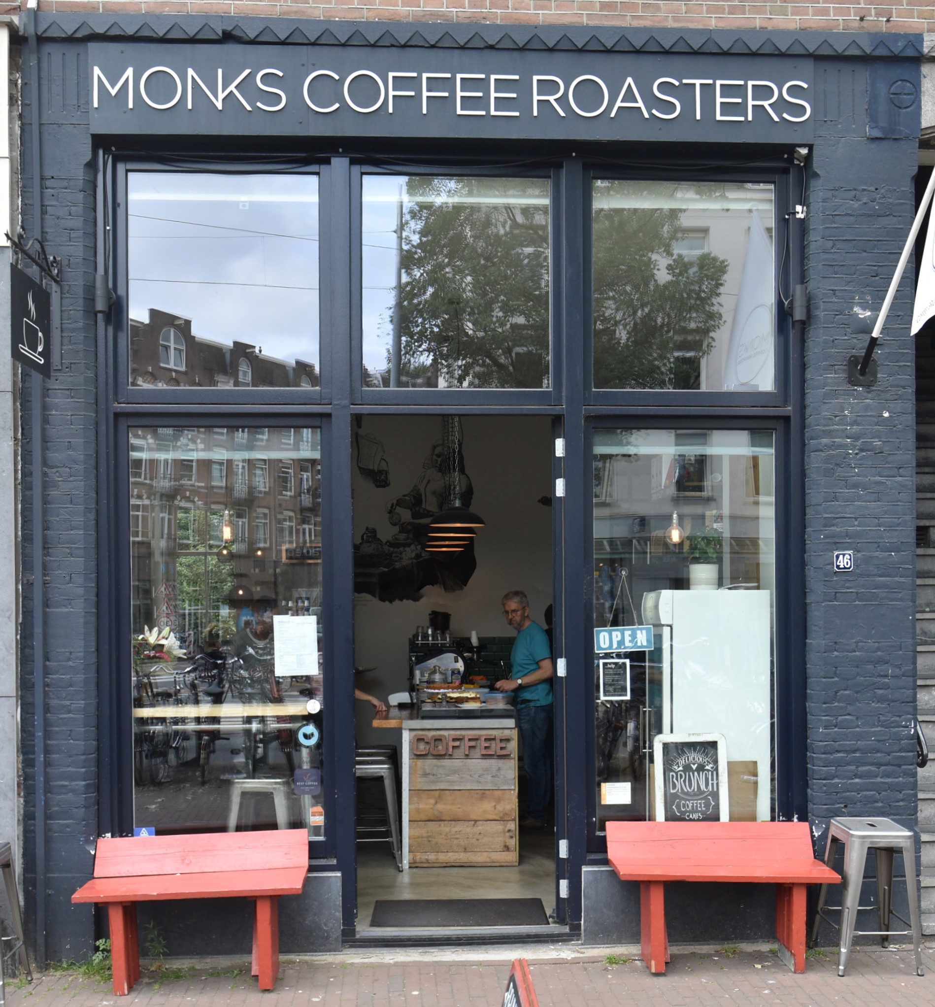 Monks Coffee Roasters on Bilderdijkstraat in Amsterdah, with benches either side of the door and the counter clearly visible.
