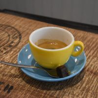 My espresso, a single-origin Honduras from Clifton Coffee Roasters, served in an over-sized yellow up on a blue saucer, with a bite-sized piece of chocolate brownie at Woof Coffee in Teddington.