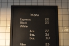 An amazingly concise coffee menu, hanging on the wall behind the counter.