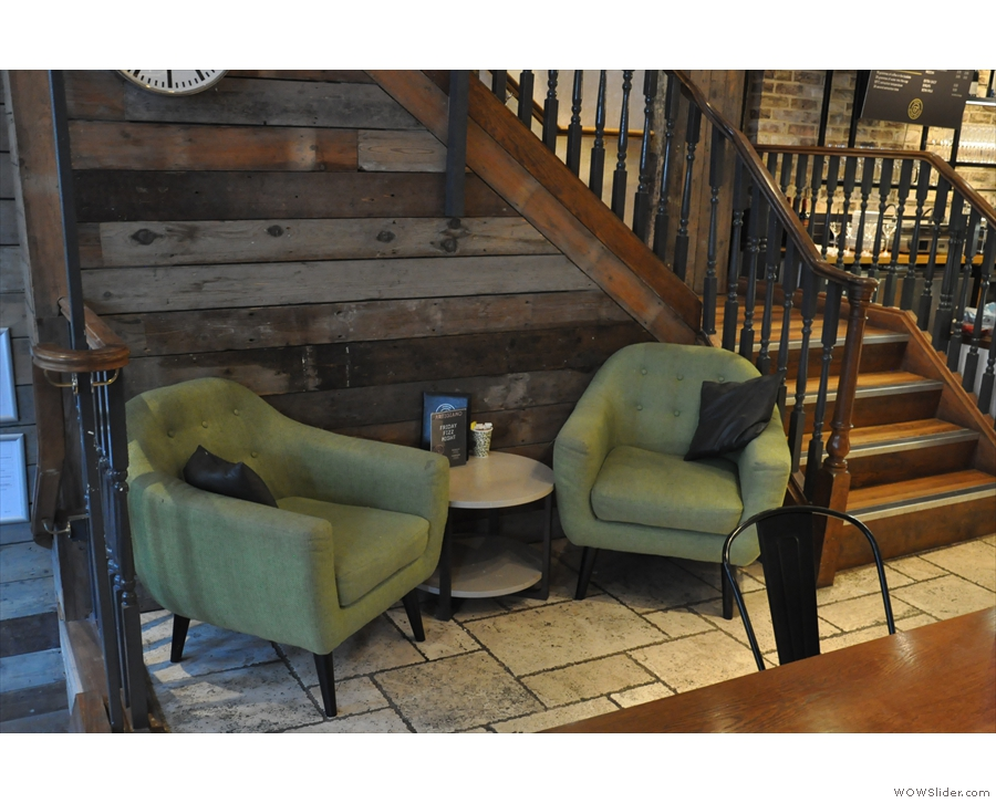 There are more tables to the left, between windows and stairs, plus these lovely armchairs.