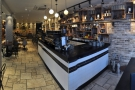 The coffee counter is on the right-hand side, with more seating beyond it.