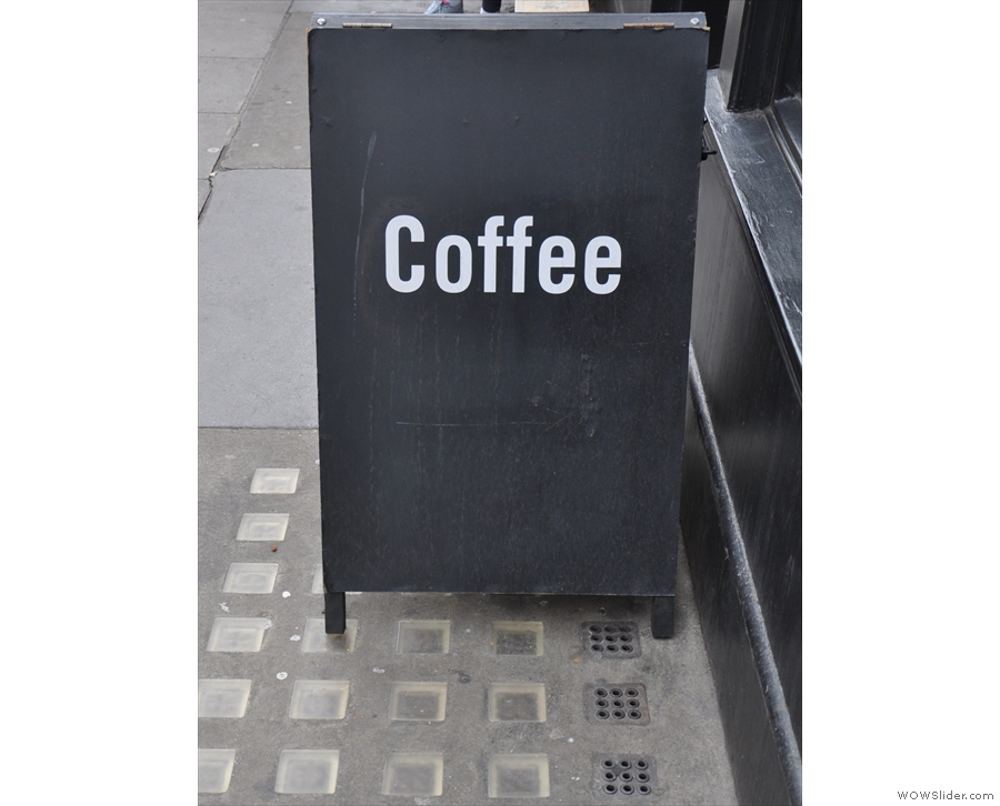 There's a solitary bench outside, with a solitary A-board & a solitary word on the A-board. However, if you can only have one word on your A-board, what better word than 'coffee'?