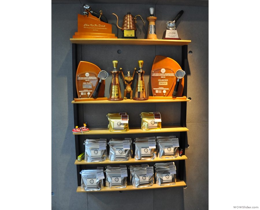 The shelf on the left-hand wall holds bags of coffee and displays various awards.