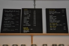 The coffee and hot drinks menus are on the wall behind the counter.