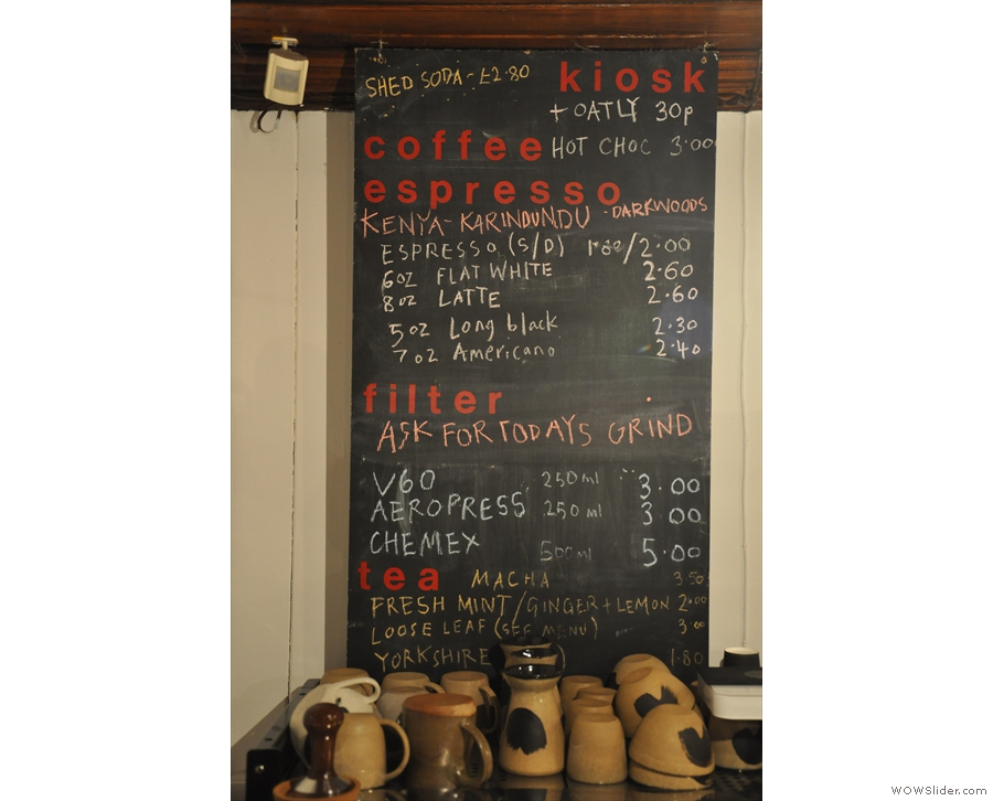 The concise coffee/tea menu is chalked up above the espresso machine.