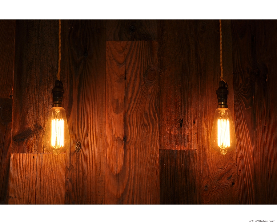 More bare light bulbs, this time to a backdrop of a wooden-clad wall.